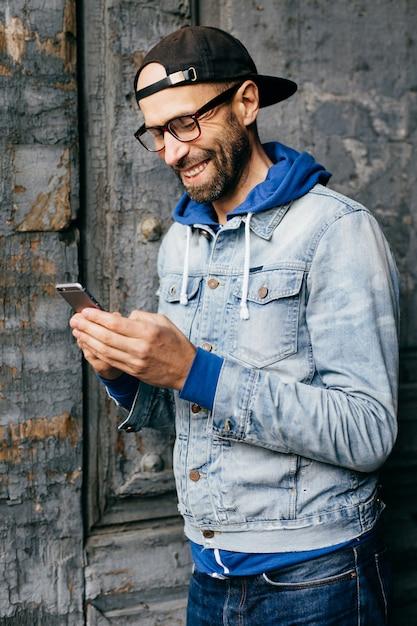 Vertikales porträt des hippie-kerls im denimhemd, -kappe und -eyewear, die modernes telefon in seinen händen halten Premium Fotos