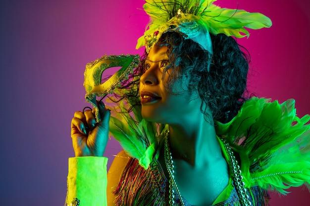 Verträumt. schöne junge frau im karneval, stilvolles maskeradenkostüm mit federn, die auf gradientenwand in neon tanzen. konzept der feiertagsfeier, der festlichen zeit, des tanzes, der party, des spaßes. Kostenlose Fotos