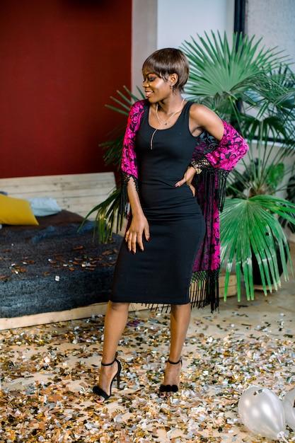 Verträumtes afrikanisches mädchen im schwarzen kleid feiern, wunsch machen. frauentag, happy new year geburtstag mockup urlaub party konzept Premium Fotos