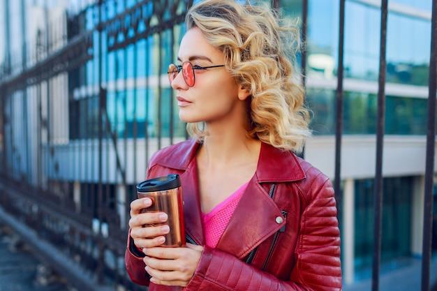 Verträumtes blondes mädchen, das die straßen geht, kaffee oder cappuccino trinkend. stilvolles herbstoutfit, lederjacke und strickpullover. rosa sonnenbrille. Kostenlose Fotos
