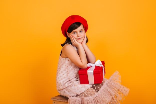 Verträumtes kind, das mit geburtstagsgeschenk aufwirft. preteen mädchen in der roten baskenmütze, die neujahrsgeschenk hält. Kostenlose Fotos