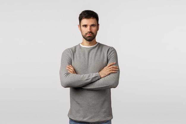 Vertrauen, mut und motivation konzept. ernst aussehender hübscher starker ernster bärtiger mann in grauer strickjacke, professionell und entschlossen aussehen, arme über der brust kreuzen, durchsetzungsfähige bereitschaftshaltung Premium Fotos