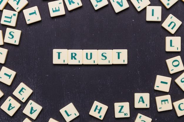 Vertrauen sie das wort, das auf dem schwarzen hintergrund vereinbart wird, der durch scrabblebuchstaben umgeben wird Kostenlose Fotos