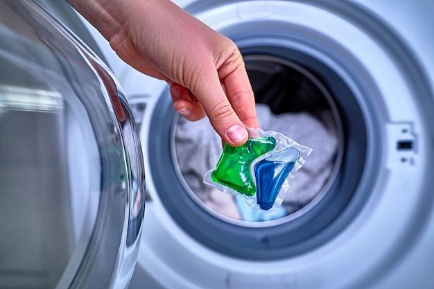 Verwenden sie eine waschpulverkapsel zum waschen bunter kleidung Premium Fotos