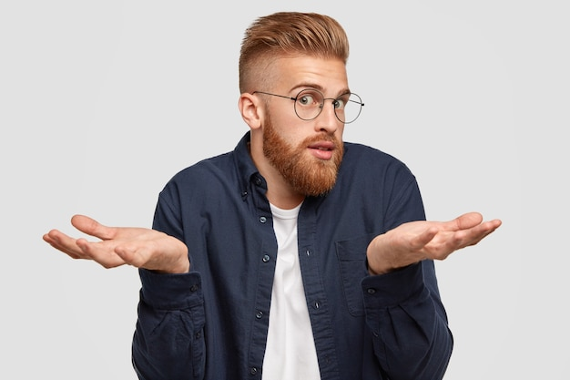 Verwirrt bärtiger ingwer männlich in brille sieht überraschend aus, zuckt verwirrt mit den schultern, zögert über etwas, hat zweifelhaften ausdruck Kostenlose Fotos