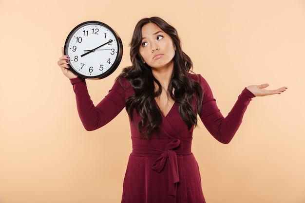 Verwirrte brunettefrau mit dem gelockten langen haar, welches die uhr zeigt zeit nach dem gestikulieren 8 hält, wie sie spät ist oder sich nicht über pfirsichhintergrund interessiert Kostenlose Fotos