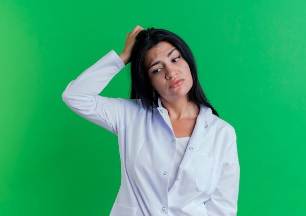 Verwirrte junge ärztin, die medizinische robe trägt, die seite berührt kopf betrachtet Kostenlose Fotos