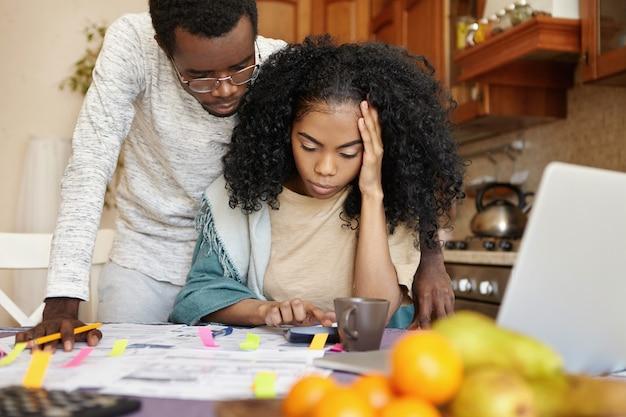 Verwirrte junge afrikanische frau, die kopfschmerzen beim berechnen des familienbudgets am küchentisch hat Kostenlose Fotos