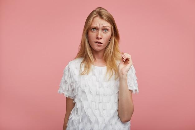 Verwirrte junge hübsche frau mit fuchsigem haar, das die augenbrauen runzelt und die unterlippe beißt, während sie mit erhobener hand über rosa hintergrund steht, gekleidet in elegante kleidung Kostenlose Fotos