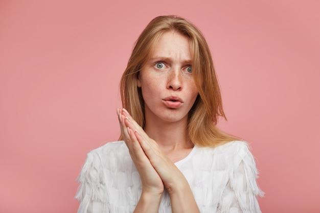 Verwirrte junge hübsche frau mit lässiger frisur, die die augenbrauen runzelt, während sie verwirrt zur kamera schaut und über rosa hintergrund mit erhabenen gefalteten handflächen steht Kostenlose Fotos