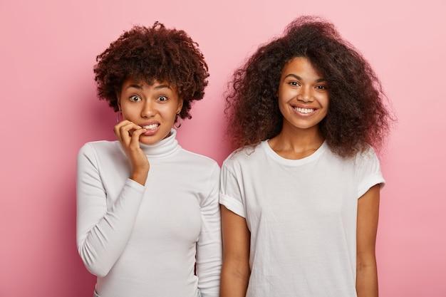 Verwirrte nervöse afroamerikanerin beißt fingernägel, schaut besorgt in die kamera, ihre fröhliche freundin mit buschigen locken steht in der nähe, trägt weiße kleidung, drückt unterschiedliche gefühle aus Kostenlose Fotos