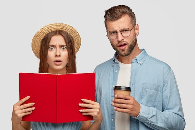 Verwirrte, unzufriedene schüler tragen ein geöffnetes buch und lesen informationen Kostenlose Fotos