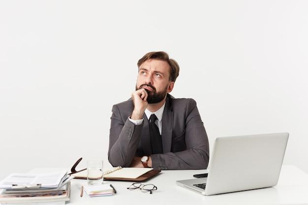Verwirrter junger bärtiger brünetter mann mit kurzem haarschnitt, der formelle kleidung und armbanduhr trägt, während am tisch mit modernem laptop und arbeitsnotizen über weißer wand sitzt Kostenlose Fotos