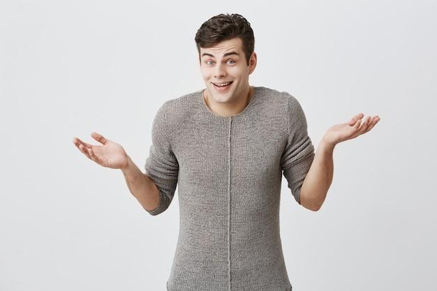 Verwirrter kaukasischer mann mit trendiger frisur im pullover, zuckt mit den schultern, hält die handflächen verwirrt offen, da er in seinem leben eine schwierige wahl trifft und nicht weiß, was er tun soll. lebenswahrnehmung und einstellung. Kostenlose Fotos