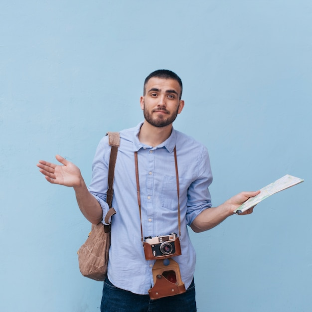 Verwirrter männlicher reisender, der seine schulter hält die karte steht gegen blaue wand zuckt Kostenlose Fotos