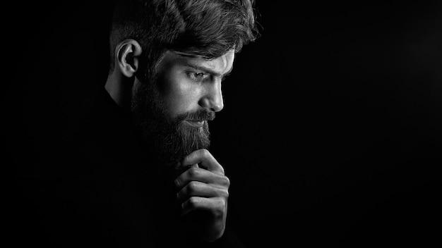 Verwirrter rührender bart des jungen mannes, der unten über schwarzem hintergrund schaut Premium Fotos