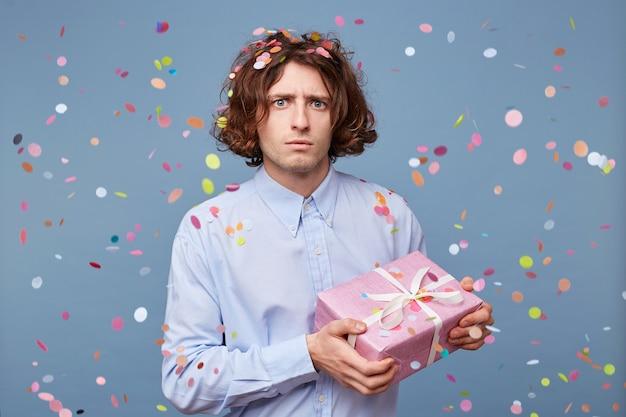 Verwirrter, verängstigter kerl, der mit einer dekorativen rosa geschenkbox posiert Kostenlose Fotos
