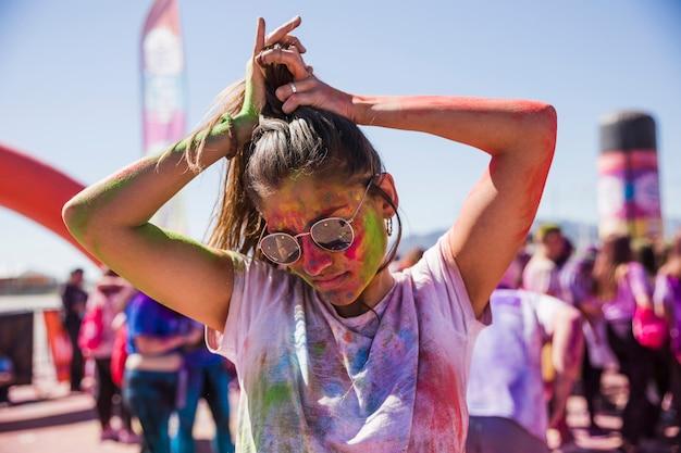 Verwirrung der jungen frau in der holi farbtragenden sonnenbrille, die draußen ihr haar bindet Kostenlose Fotos