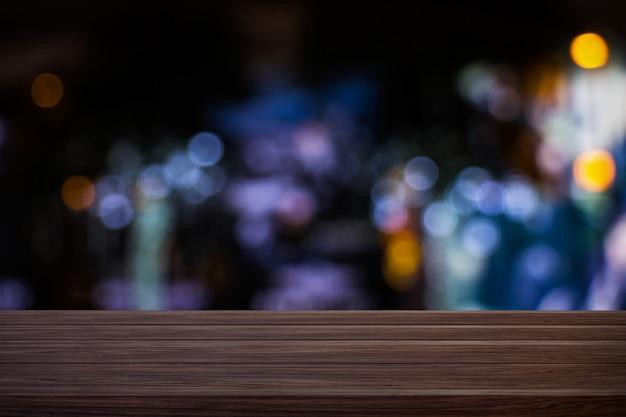 Verwischen sie das caférestaurant oder die kaffeestube, die von der hölzernen tabelle mit unscharfem hellem goldbokeh zurück leeren Premium Fotos