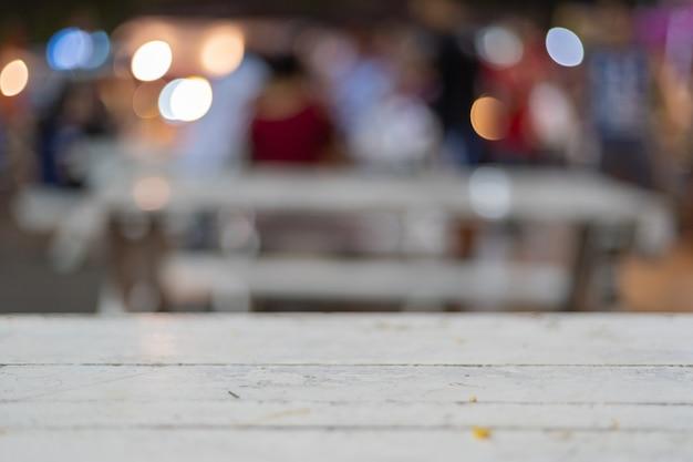 Verwischen sie den vollen hintergrund der farbe mit weißem hölzernem tabellenvordergrund nachts. Premium Fotos