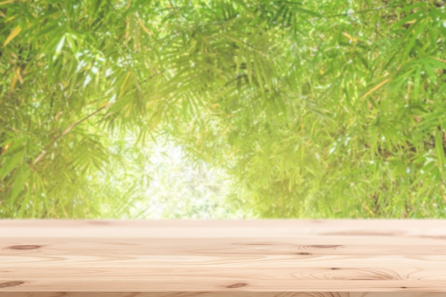 Verwischen sie grünes naturbambusblatt mit holztisch für anzeige im natürlichen umweltfreundlichen produkthintergrund. Premium Fotos