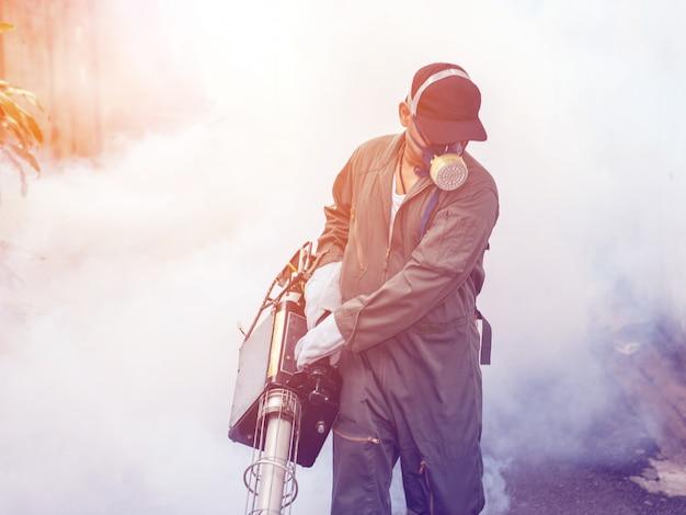 Verwischt von der mannarbeit, die vernebelt, um moskito zu beseitigen Premium Fotos