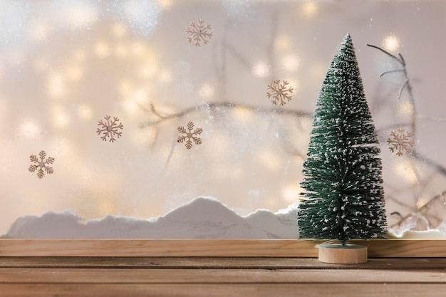 Verzieren sie tannenbaum auf hölzerner tabelle nahe bank des schnees, des betriebszweigs, der schneeflocken und der feenhaften lichter Kostenlose Fotos