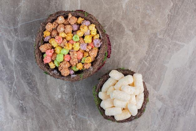 Verzierte schalen mit maissnacks und mit süßigkeiten überzogenen popcorns auf marmor. Kostenlose Fotos