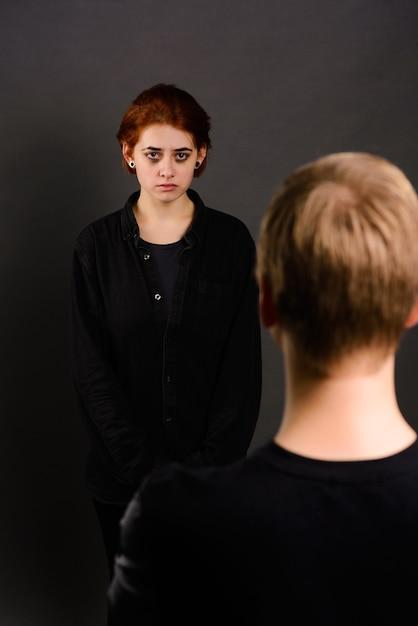 Verzweifelte junge frau mit aggressivem mann im studio, konzeption häuslicher gewalt Premium Fotos