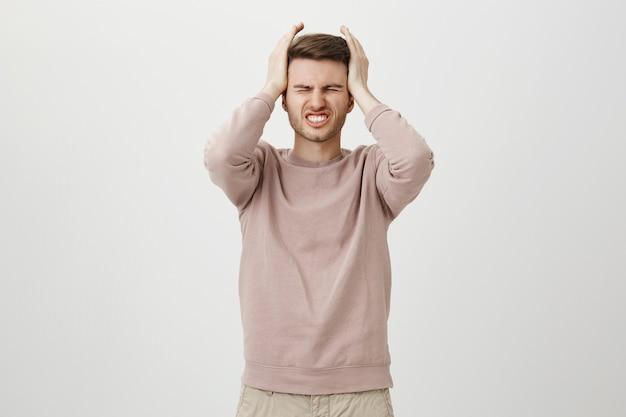 Verzweifelter verzweifelter kerl drückt bedauern aus, hält hände auf dem kopf enttäuscht Kostenlose Fotos