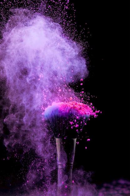 Vibrierender impuls des make-uppuders mit bürste auf dunklem hintergrund Kostenlose Fotos