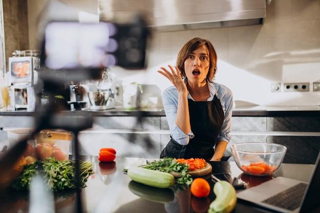 Videoblogger der jungen frau, der an der küche kocht und filmt Kostenlose Fotos
