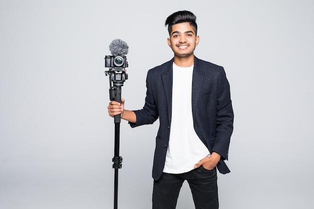 Videokamera-betreiber des jungen indischen mannes lokalisiert auf weißem hintergrund. Kostenlose Fotos