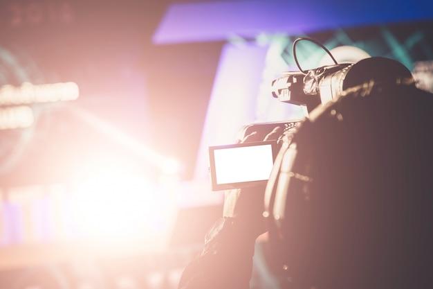 Videokamerabediener, der mit seiner ausrüstung im preiszeremoniethema kreativ arbeitet Premium Fotos