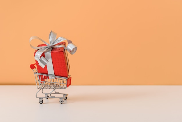 Viel geschenkbox mit rotem bandbogen und warenkorb oder laufkatze auf weißer tabelle und orange pastellhintergrund Premium Fotos