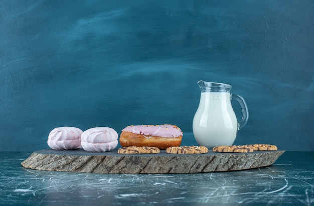 Viel süßes süßwaren mit milch auf einem dunklen brett. hochwertiges foto Kostenlose Fotos