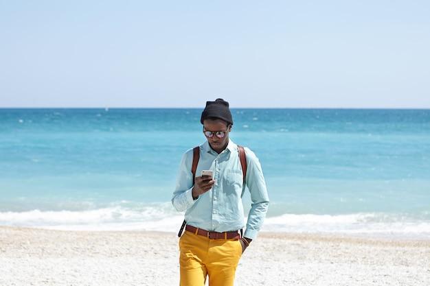 Vielbeschäftigter junger dunkelhäutiger europäer, der modische, trendige kleidung und einen rucksack trägt und auch in den ferien online bleibt, am strand ein mobiltelefon benutzt und alle schönheiten ignoriert, die ihn umgeben Kostenlose Fotos