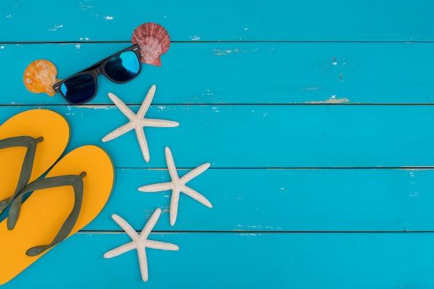 Viele arten muschel, sonnenbrille und starfish auf blauem rustikalem hölzernem hintergrund. Premium Fotos