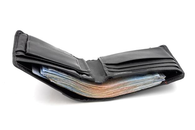 Viele banknoten in der schwarzen geldbörse auf weißem hintergrund Premium Fotos
