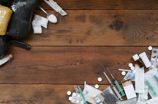 Viele betäubungsmittel und geräte zur herstellung von drogen auf einem alten holztisch Premium Fotos