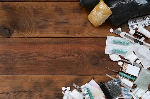 Viele betäubungsmittel und vorrichtungen zur herstellung von arzneimitteln liegen auf einem alten holztischhintergrund Premium Fotos