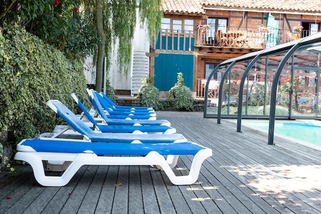 Viele blaue liegestühle neben dem pool Premium Fotos