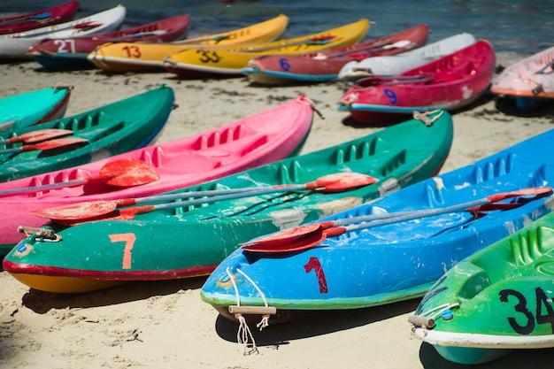 Viele bunte alte kanus kajaks am strand Premium Fotos