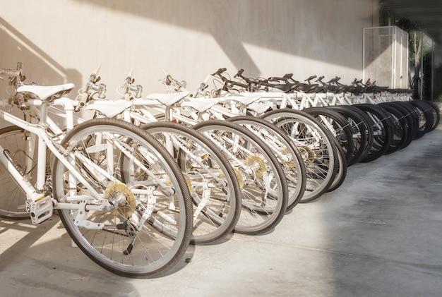Viele fahrräder in einer reihe. schwarz-weiß-fahrräder stehen auf einem parkplatz für kunden. Premium Fotos