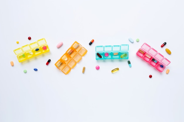 Viele farbigen tabletten und kapseln mit dem pillenkasten lokalisiert auf weiß Premium Fotos