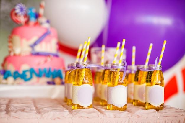Viele flaschen apfelsaft, spezielle etiketten darauf, weiße und gelbe strohhalme, großer rosa kuchen und weiße und lila luftballons Premium Fotos
