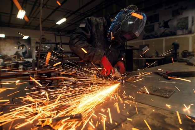 Viele funken und fokussierte professionelle industriearbeiter mit schutzmaske, die mit einer elektrischen schleifmaschine in einer stoffwerkstatt arbeiten Premium Fotos