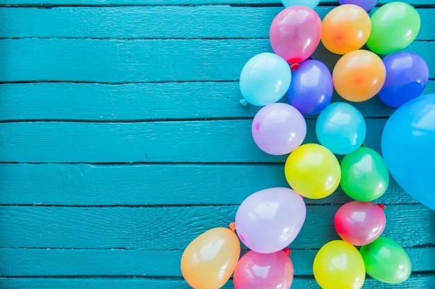 Viele geblasene ballone auf gemaltem blauem hölzernem hintergrund Kostenlose Fotos