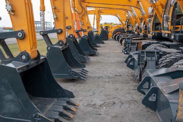 Viele gelbe traktoren oder bagger auf einer ausstellung Premium Fotos