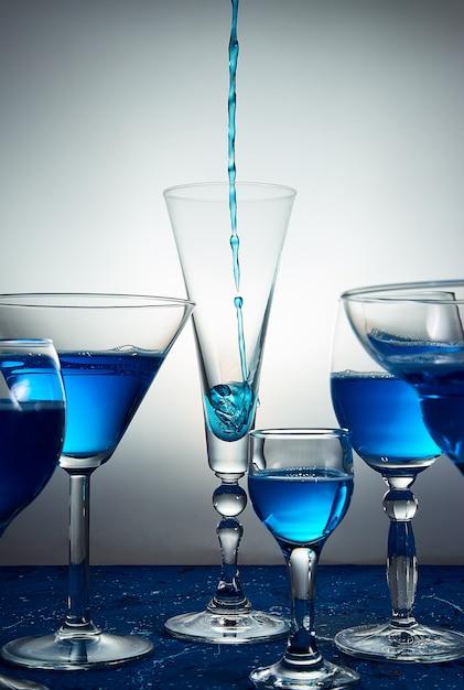 Viele gläser mit blauem champagner oder cocktail. Premium Fotos